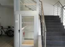 Platforma pionowa w szybie panoramicznym, zainstalowana w duszy klatki schodowej