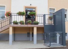 Mała platforma pionowa JURA 14.10, zainstalowana przy schodach zewnętrznych budynku gminy